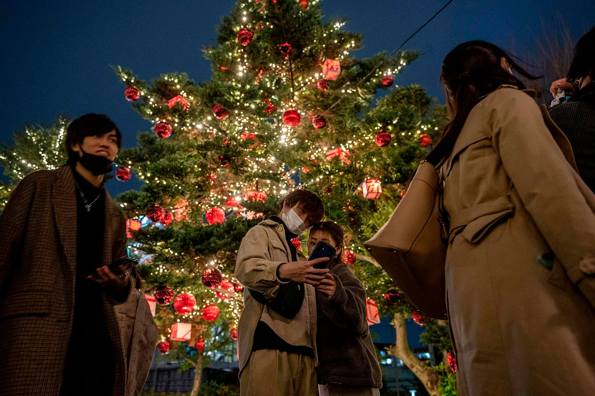 A couple takes pictures with Christmas-themed illuminated trees on Christmas eve, in Roppongi district of Tokyo