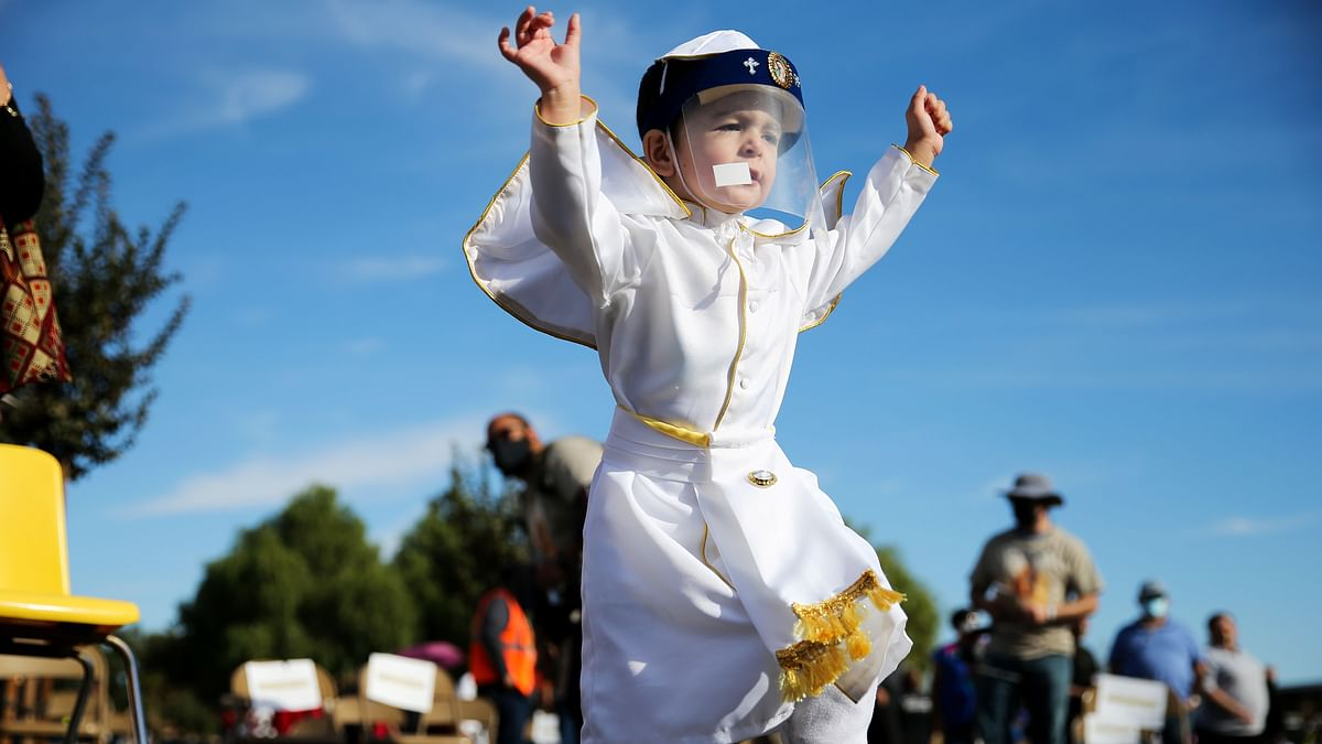 A two-yr-old boy with a face shield participates in traditional procession and mass in honor of Our Lady of Guadalupe in San Gabriel, California.