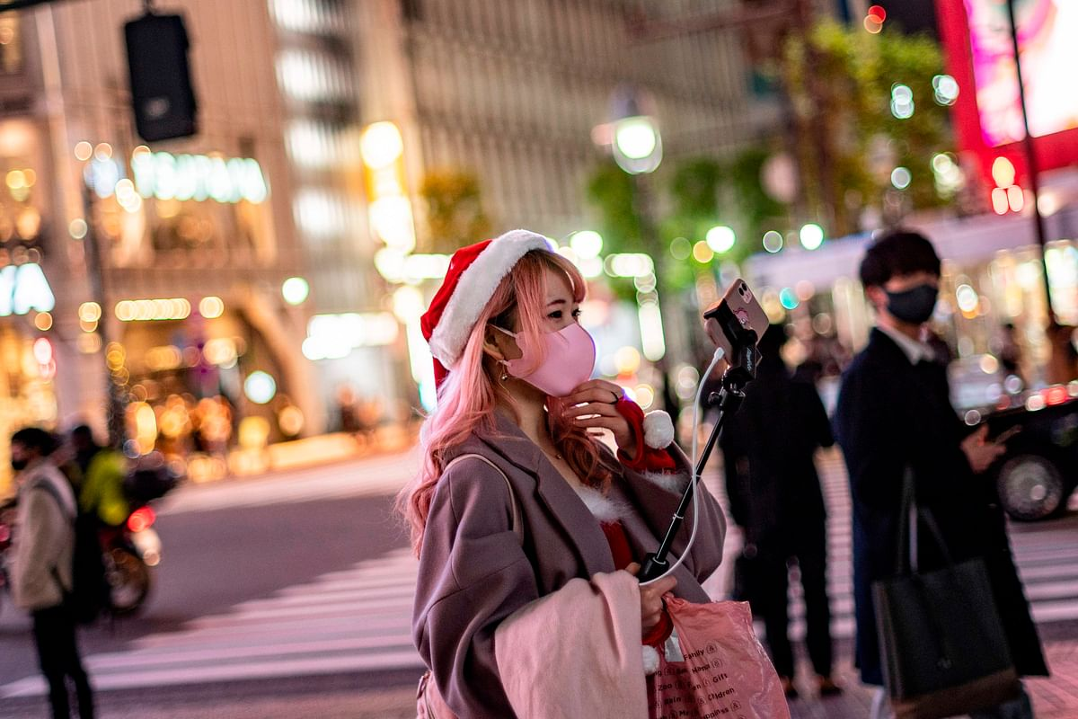 A woman wearing a Santa hat takes video clips on Christmas eve, in Shibuya district of Tokyo