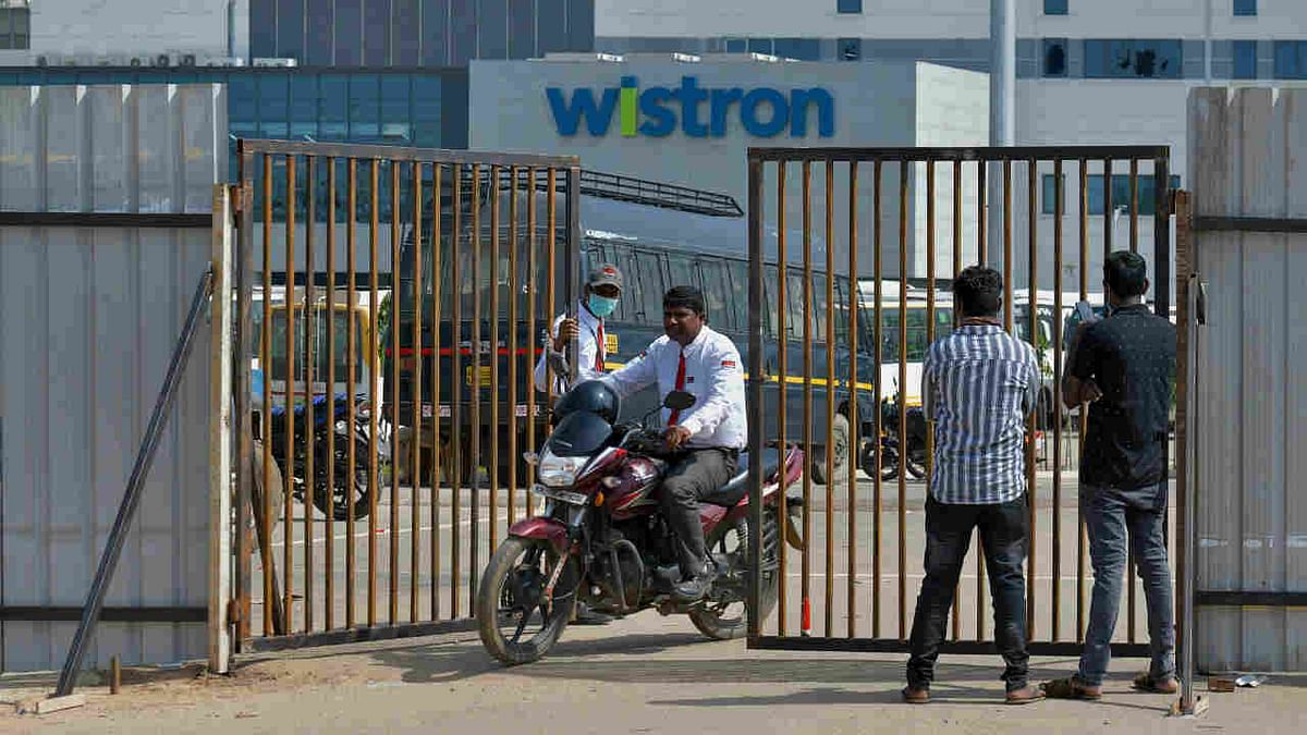 People exit from the gate of Wistron, a Taiwanese-run iPhone factory at Narsapura, about 60 km from Bangalore on December 13, 2020