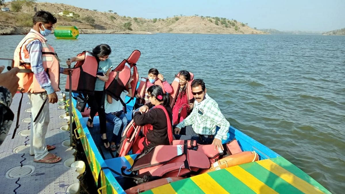 Tourist enjoying boat ride on the opening day of Paryatan Mahotsav at Dholawad reservoir near Ratlam on Saturday