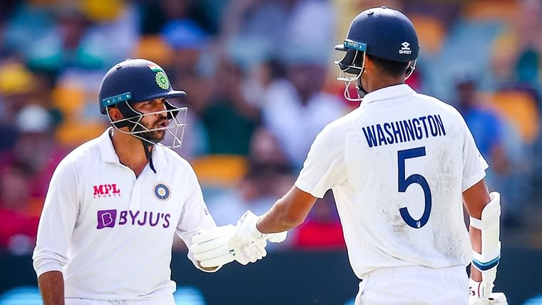 Washington Sundar (R) is congratulated by Shardul Thakur (L) after reaching his half century during day three of the fourth cricket Test match between Australia and India at the Gabba in Brisbane