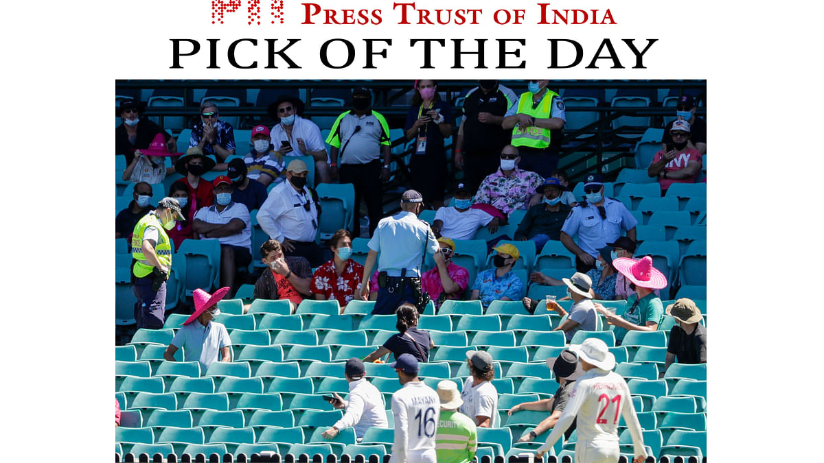 Police talk to spectators as the game is stopped after a complaint by Indian players during play at SCG on Sunday