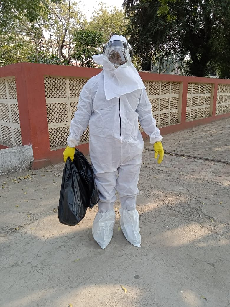 An employee present for bird flu controlling drive collected the dead crows by wearing a PPE kit to avoid the spread of virus.
