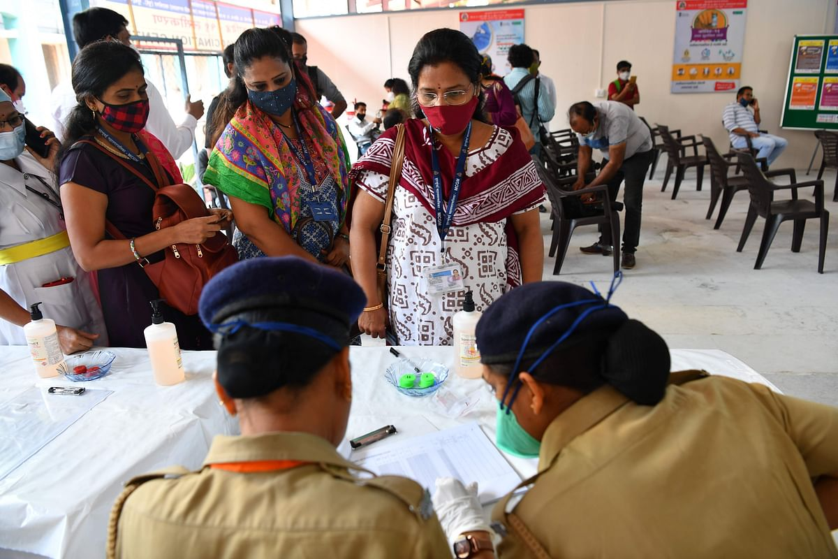 Health workers in line to receive the Covid-19 coronavirus vaccine verify their identities at a vaccination centre in the Rajawadi Hospital in Mumbai on January 16, 2021.