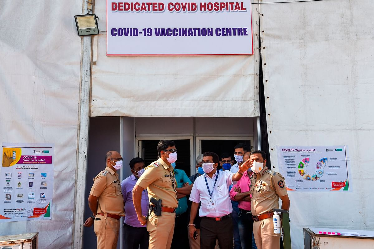 Medical staff and policemen speak at a Covid-19 coronavirus vaccination centre in Mumbai on January 15, 2021, a day before India starts the first phase of vaccination across the country.