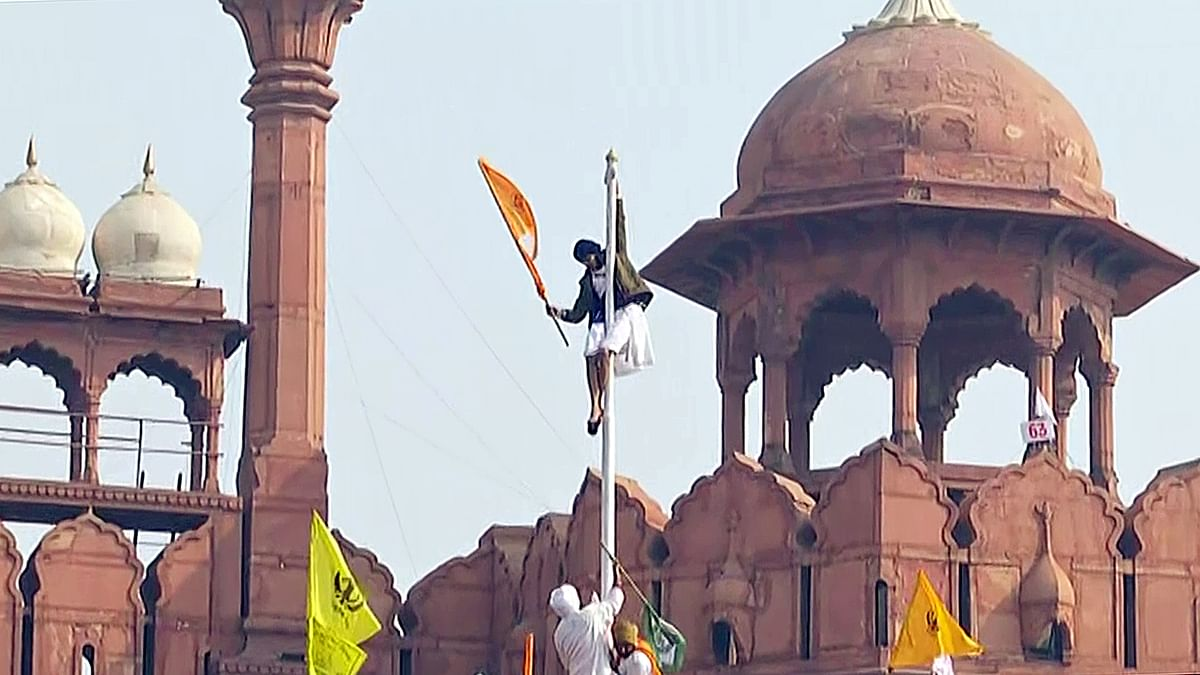 Protesting farmers hoist a flag from the ramparts of the Red Fort on 72nd Republic Day, in New Delhi on Tuesday.
