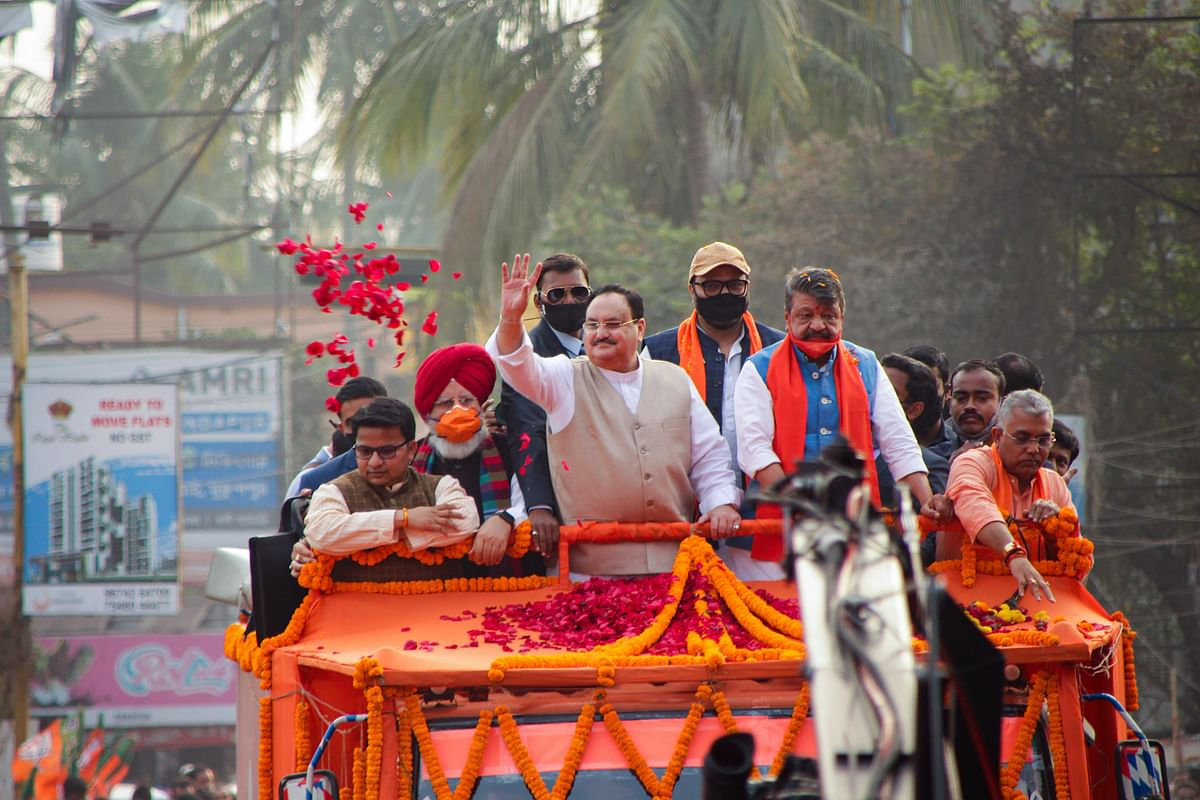 BJP National President J.P. Nadda throws flowers on his supporters during a roadshow, in Bardhaman