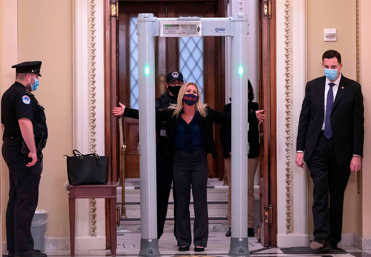 Representative Marjorie Taylor Greene goes through security outside the House Chamber at Capitol Hill in Washington.