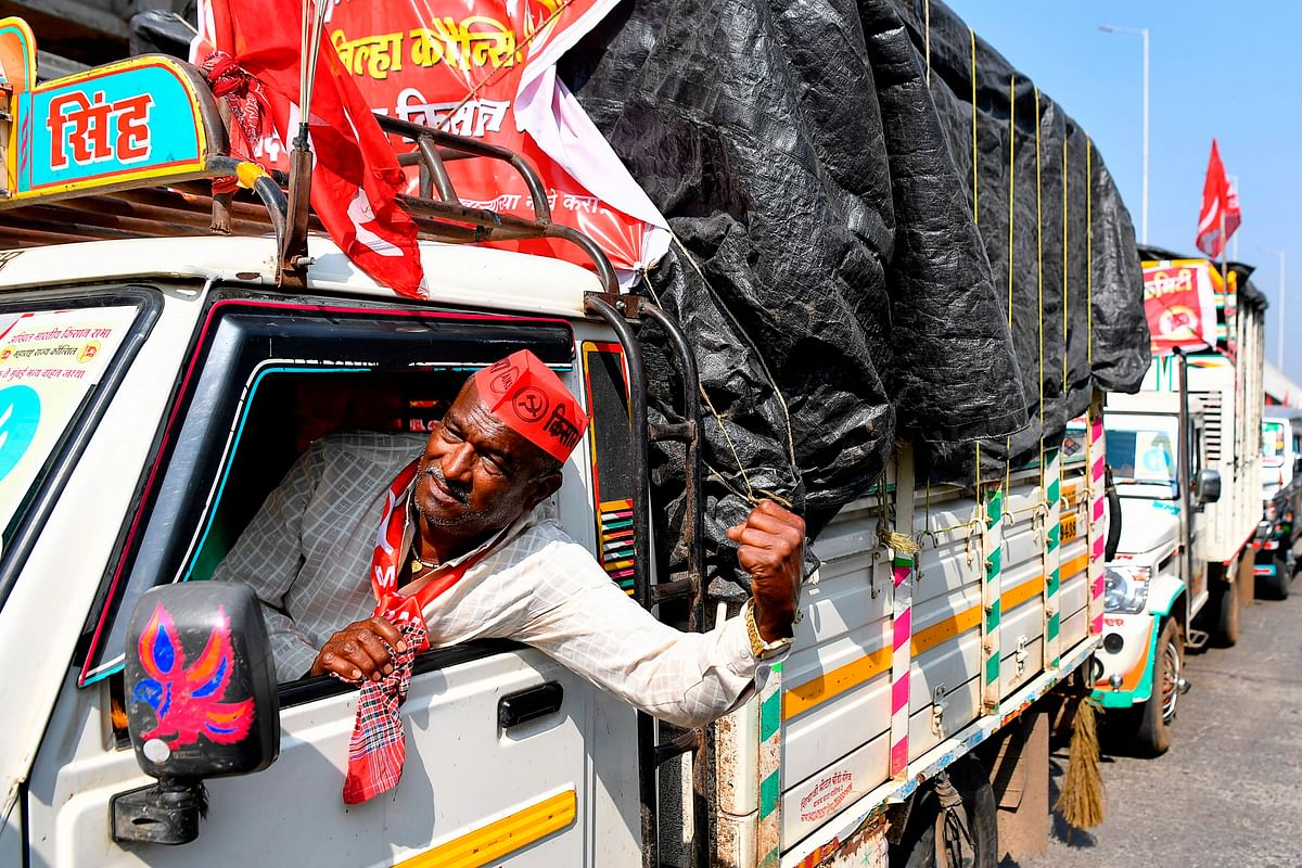 A farmer shouts slogans inside a vehicle as he crosses along with others a state highway during a rally to Mumbai in support of farmers who are continuing their protest against the central governments recent agricultural reforms, at Bhiwandi in the Thane district of Maharashtra on January 24, 2021.