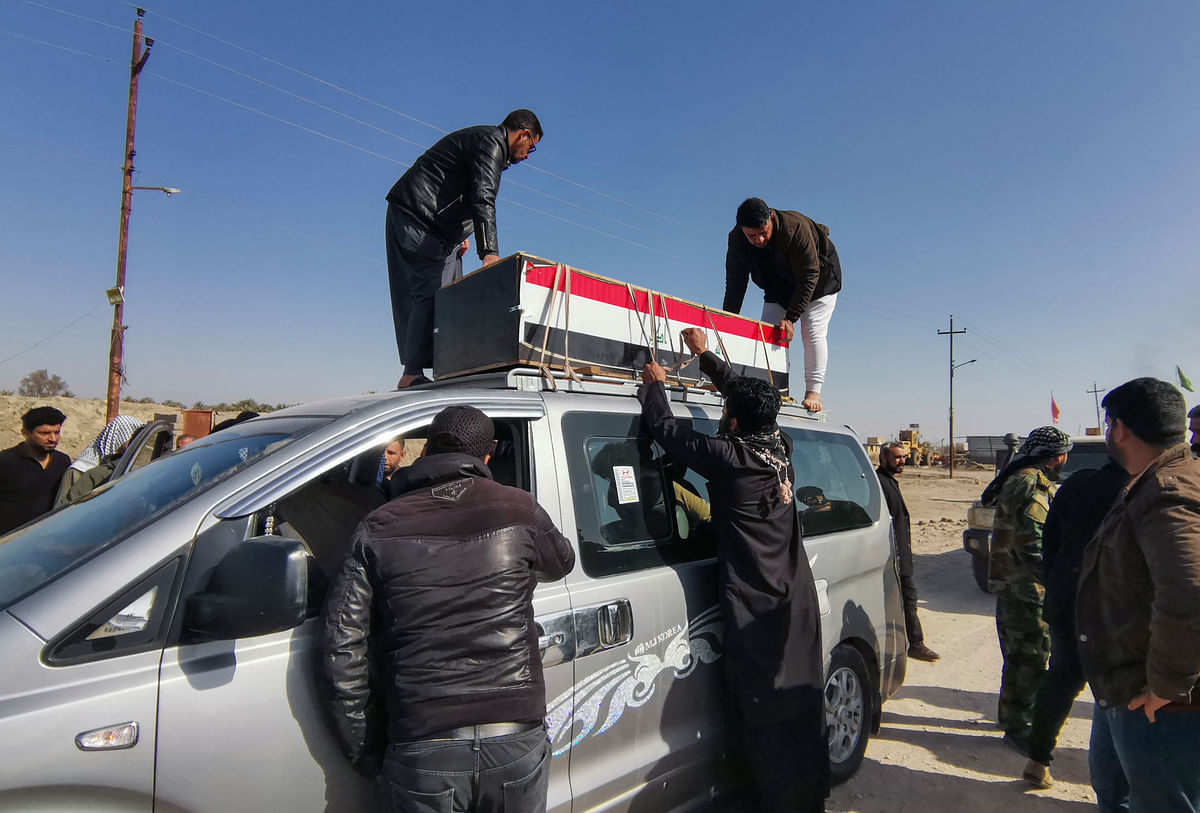 Iraqi mourners arrive in a funerary convoy transporting the body of a member of the Hashed al-Shaabi force for burial in the southern city of Nasiriyah in the Dhi Qar province, on January 24.