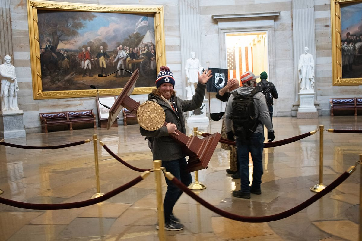 A pro-Trump protester carries the lectern of U.S. Speaker of the House Nancy Pelosi through the Roturnda of the U.S. Capitol Building