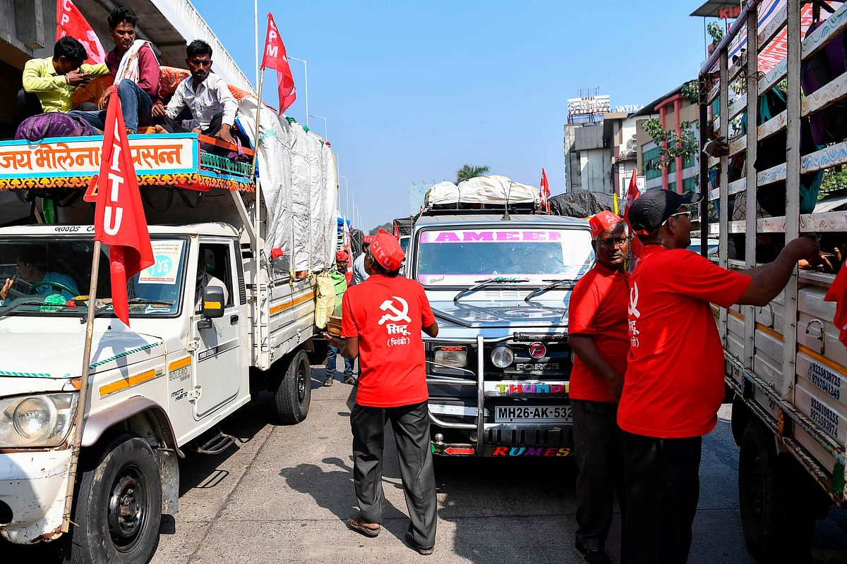 Volunteers distribute food to farmers sitting in vehicles as they cross a state highway during a rally to Mumbai in support of farmers who are continuing their protest against the central governments recent agricultural reforms, at Bhiwandi in the Thane district of Maharashtra on January 24, 2021