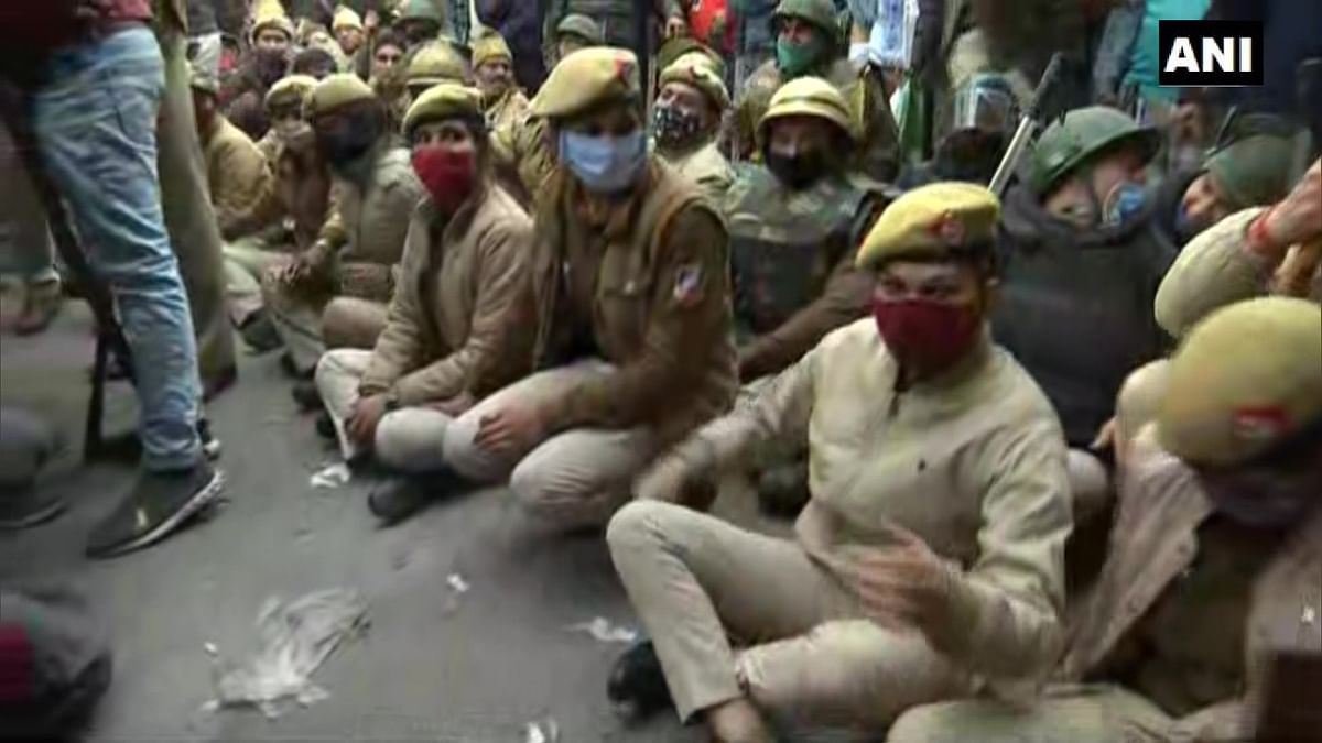 Delhi: Police officials sit on road in Nangloi to block the area