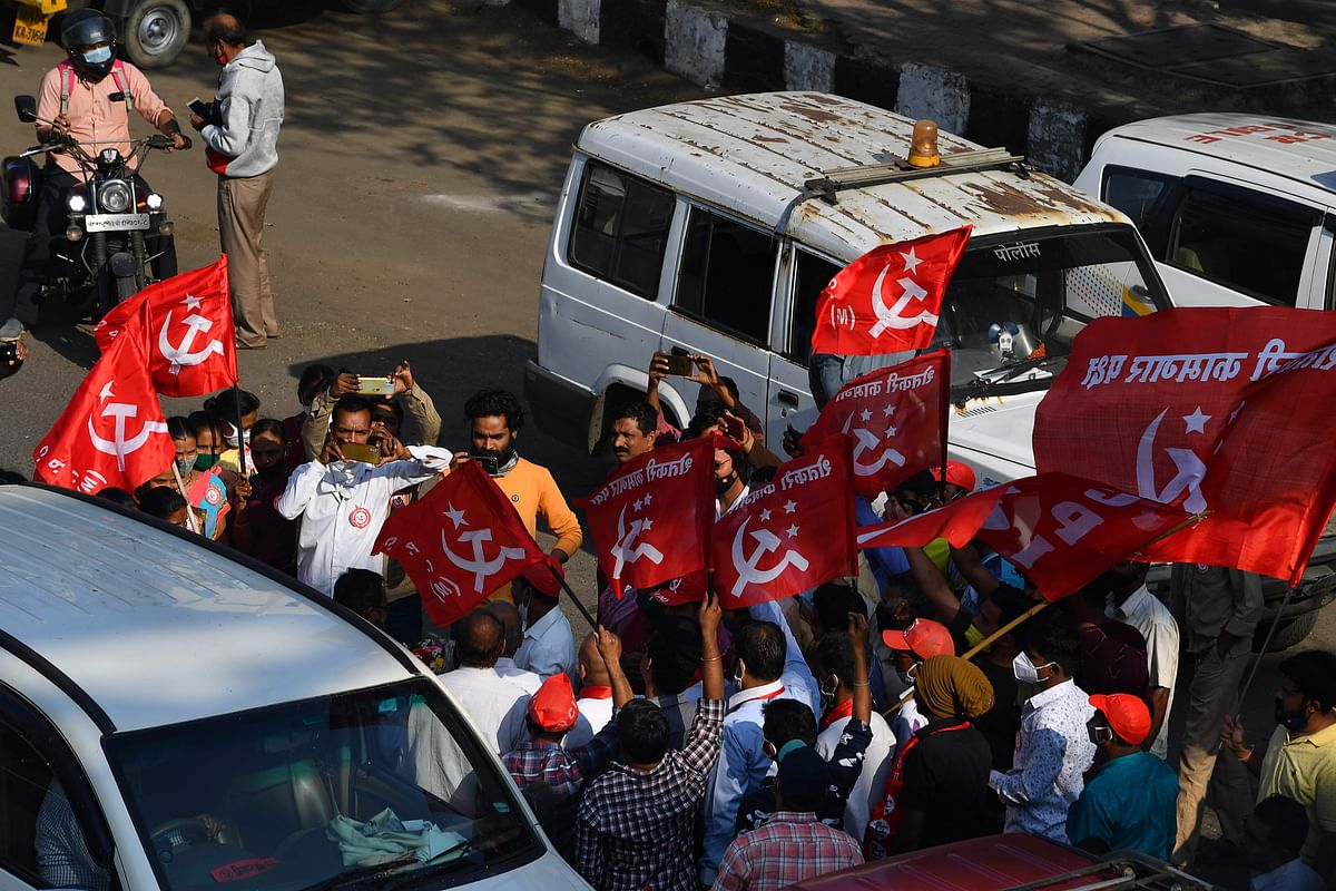 Passersby and members of the left-wing trade Union welcome farmers arriving after crossing a state highway during a rally in support of farmers who are continuing their protest against the central governments recent agricultural reforms, at Bhiwandi in the Thane district of Maharashtra on January 24, 2021.