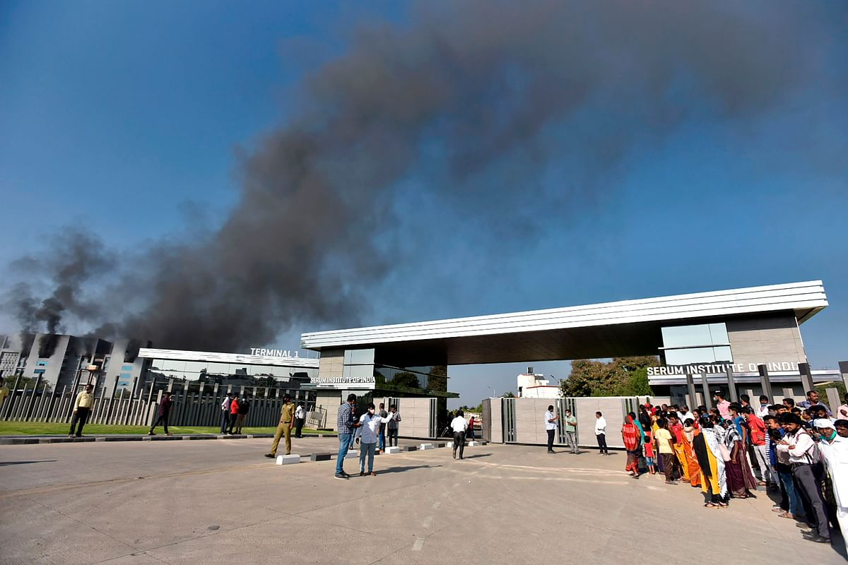 People stand as smoke rises after a fire broke out at Indias Serum Institute in Pune on January 21, 2021. - A fire broke out on January 21 at Indias Serum Institute, the worlds largest maker of vaccines, but a company source said production of drugs to prevent Covid-19 coronavirus was not affected