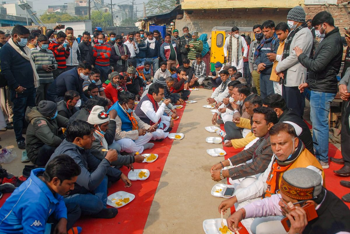 BJP MLA Pankaj Singh (5L) having a meal with the residents of a locality on Makar Sankranti, in Noida, Thursday, Jan. 14, 2021. (PTI Photo)