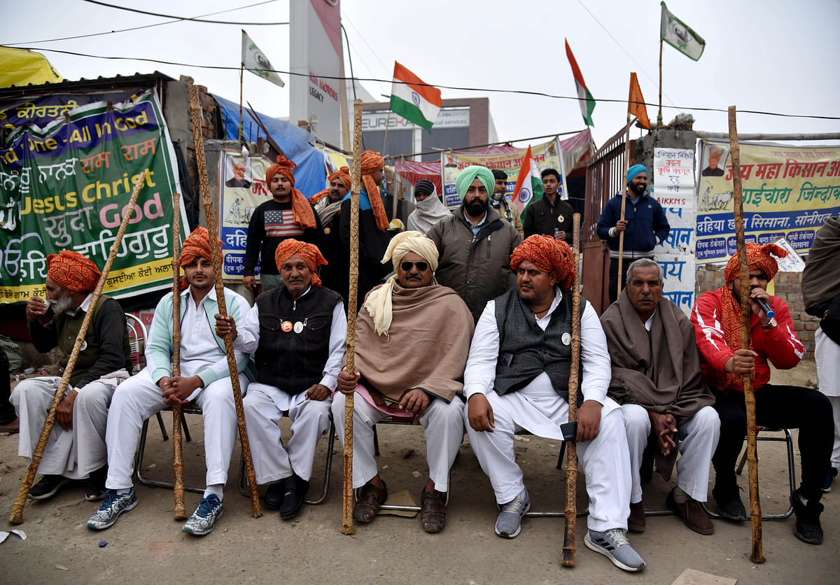 New Delhi, Jan 24 (ANI): Farmers sit with their long heavy wooden stick at the demonstration site where they are protesting against the new farm laws at Singhu Border, in New Delhi.