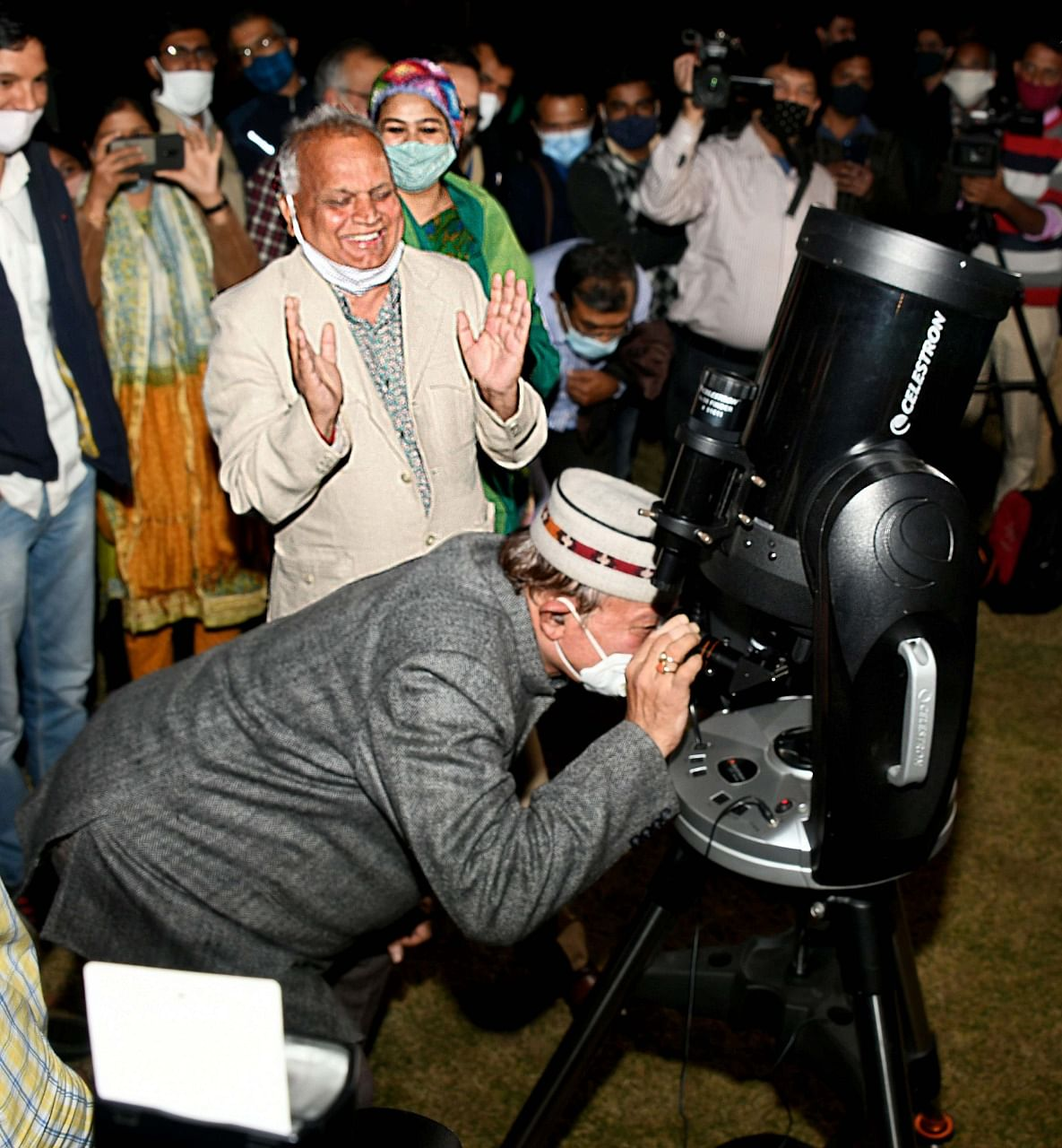 Art and Culture minister Dr. B.D. Kalla looking at the night sky through the telescope. To this left, chief secretary Niranjan Arya.