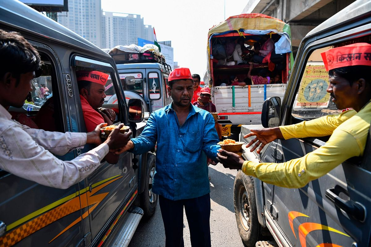 A volunteer (C) distributes food to farmers sitting in vehicles as they cross a state highway during a rally to Mumbai in support of farmers who are continuing their protest against the central governments recent agricultural reforms, at Bhiwandi in the Thane district of Maharashtra on January 24, 2021.
