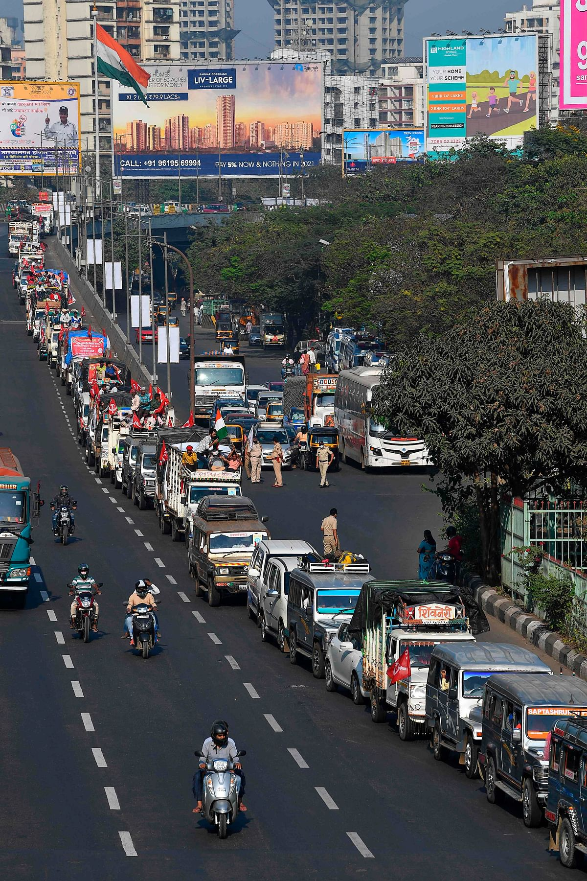 Farmers in vehicles cross a state highway during a rally to Mumbai in support of the ongoing farmers protest against the central governments recent agricultural reformson, at Bhiwandi in the Thane district of Maharashtra on January 24, 2021
