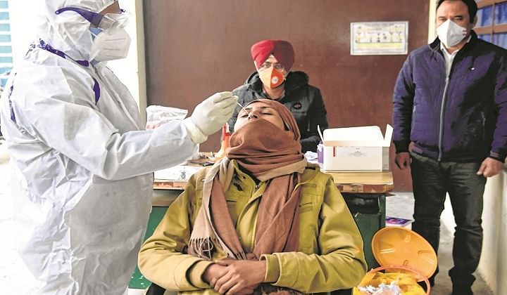 A health worker collects a nasal swab sample from a cop to test for the Covid-19 in Amritsar on Monday.