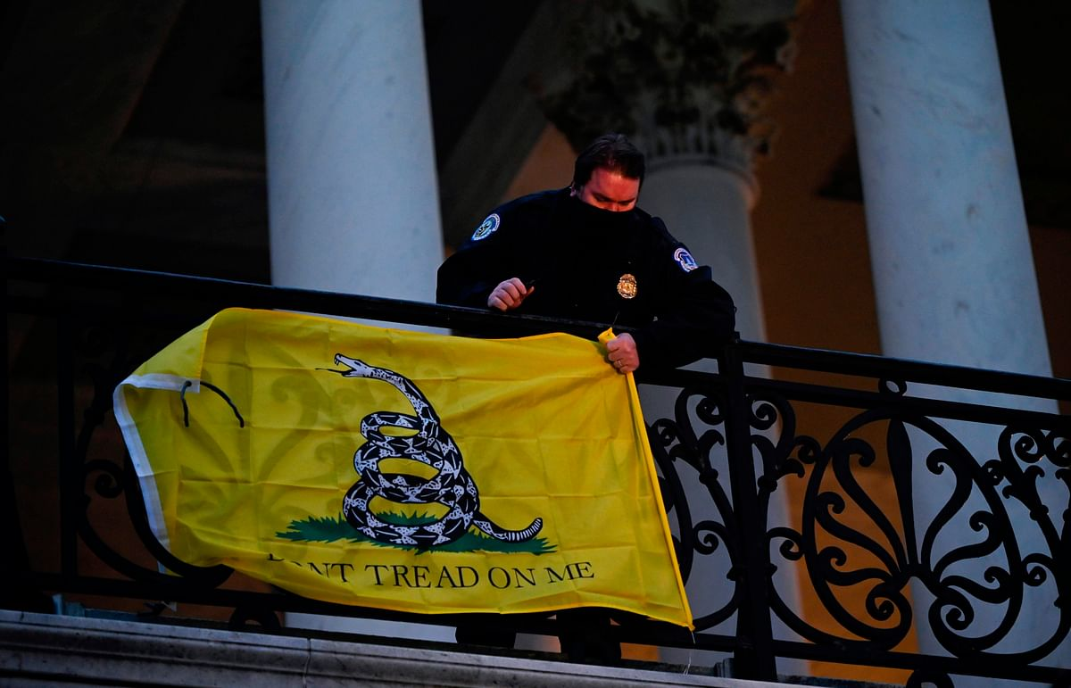 A police officer takes down a flag left hanging by protestors outside of the US Capitol in Washington DC on January 6, 2021.