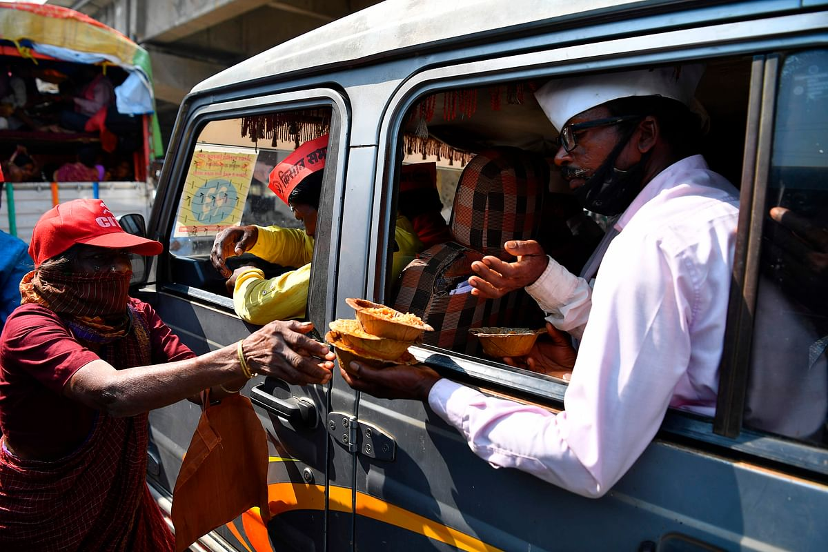 A volunteer (L) distributes food to farmers sitting in a vehicle as they cross a state highway during a rally to Mumbai in support of farmers who are continuing their protest against the central governments recent agricultural reforms, at Bhiwandi in the Thane district of Maharashtra on January 24, 2021.