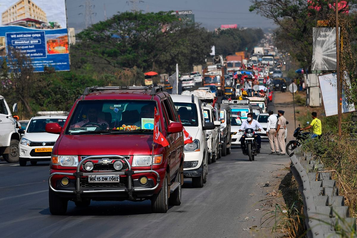 Farmers in vehicles cross a state highway during a rally to Mumbai in support of the ongoing farmers protest against the central governments recent agricultural reformson, at Bhiwandi in the Thane district of Maharashtra on January 24, 2021.