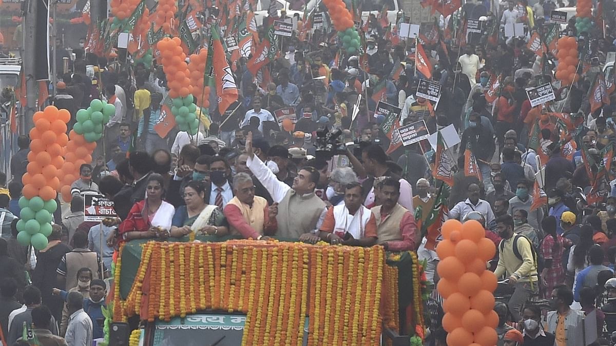 (L to R) State BJP Vice President Bharati Ghosh, West Bengal Minister Debosree Chowdhury, State Party President Dilip Ghosh, and BJP leader Suvendu Adhikary wave at party activists during a roadshow from Tollygunge tram depot to Rashbehari at South Kolkata, Monday, Jan. 18, 2021.