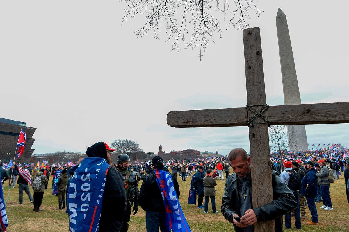 A man holds a large wooden cross near the Washington Monument during a rally in support of US President Donald Trump in Washington DC on January 6, 2021.