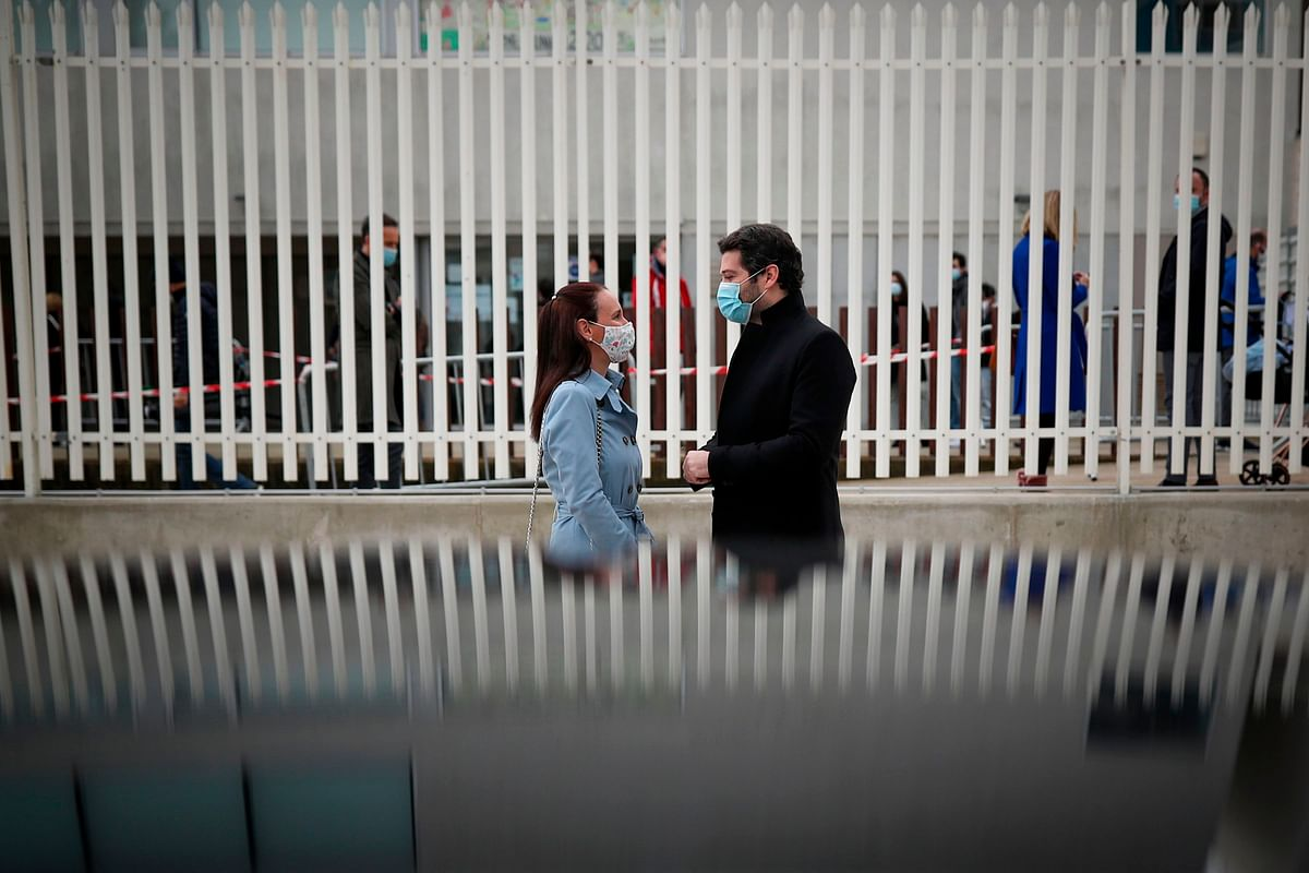 Portugal's Chega party leader and far-right presidential candidate Andre Ventura speaks to his wife Dina Ventura after casting their votes for the Portuguese presidential election in Lisbon on January 24.