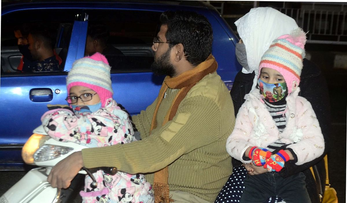 A family wearing warm clothes moves on a two-wheeler in Bhopal on Thursday.