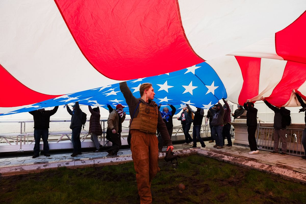 A group of pro-Trump protesters raise a giant America Flag on the West grounds of the Capitol Building on January 6, 2021 in Washington, DC.