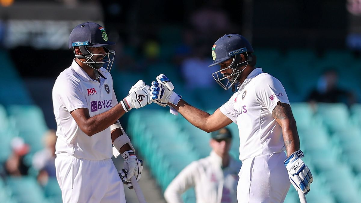 India's Ravichandran Ashwin (L) and teammate Hanuma Vihari touch gloves during the fifth day of the third cricket Test match between Australia and India at the Sydney Cricket Ground (SCG) in Sydney on January 11, 2021.