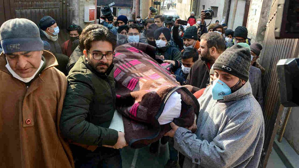 Local Muslims and relatives of Satpal Nischal carry his body, at his residence in Srinagar, Friday, Jan 1, 2021.