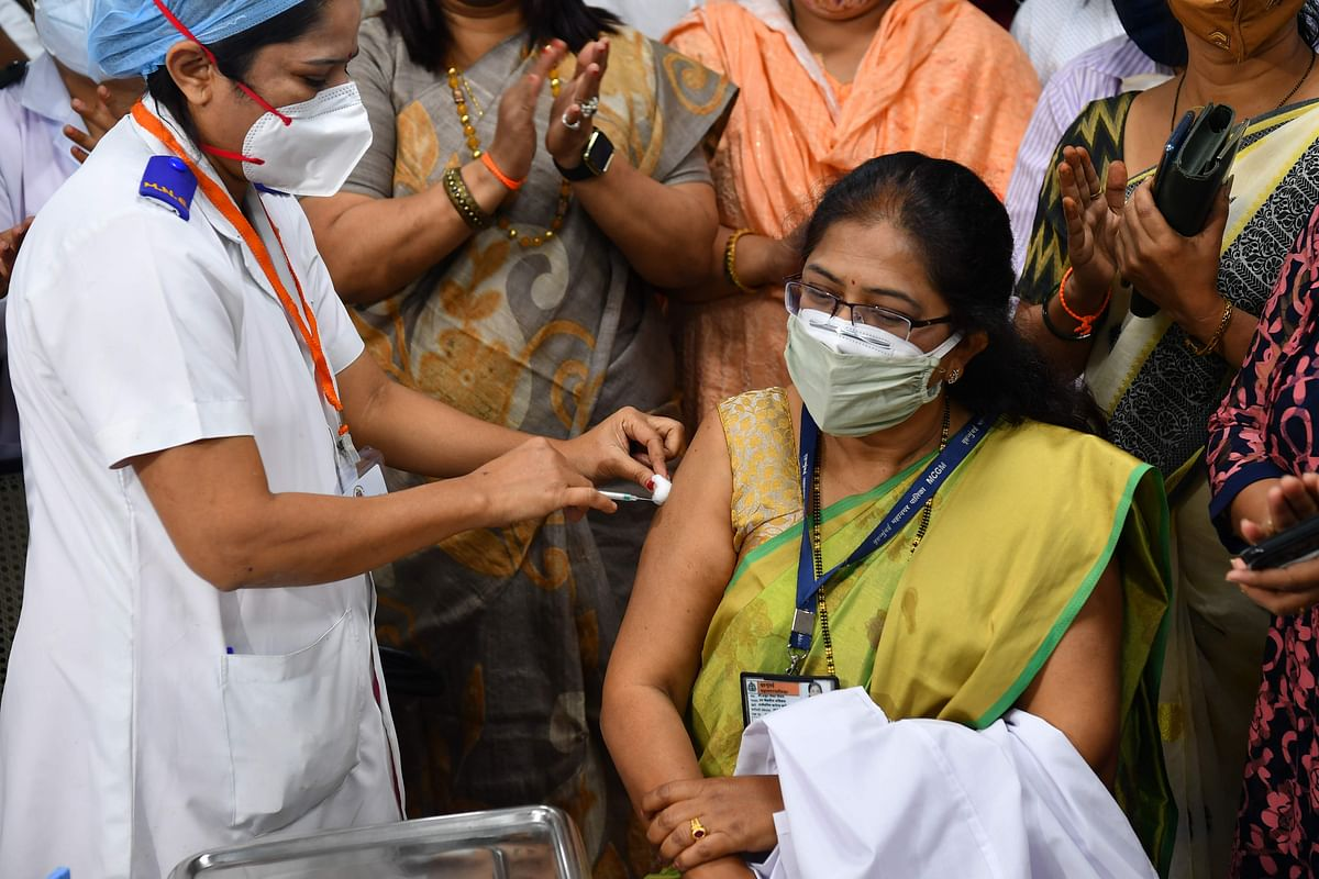 A medical worker inoculates Vidya Thakur (R), medical dean of the Rajawadi Hospital, with a Covid-19 coronavirus vaccine at the hospital in Mumbai on January 16, 2021.