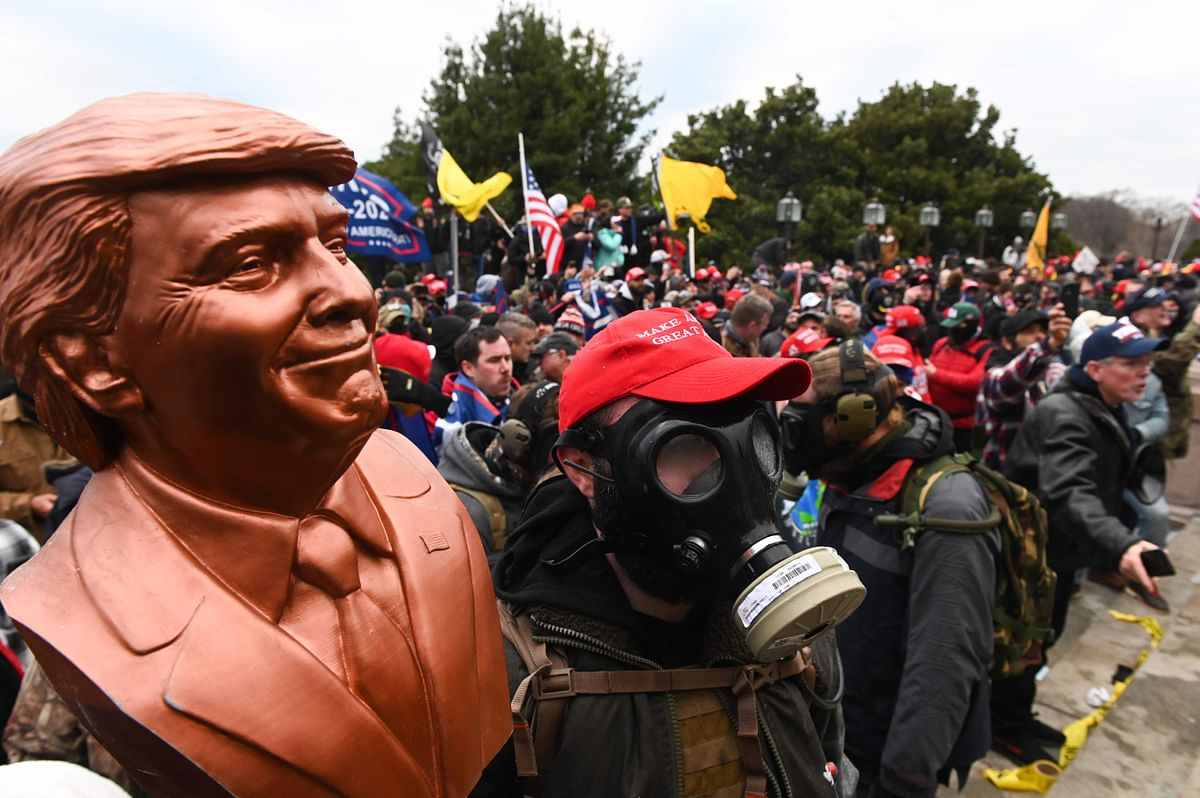 A supporter of US President Donald Trump wears a gas mask and holds a bust of him after he and hundreds of others stormed stormed the Capitol building on January 6, 2021 in Washington, DC