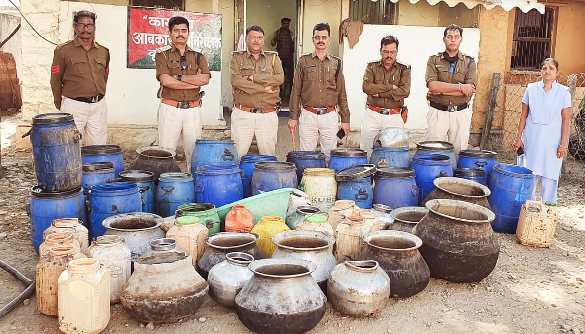District excise team with seized liquor, mahua lahan in Sanawad on Tuesday