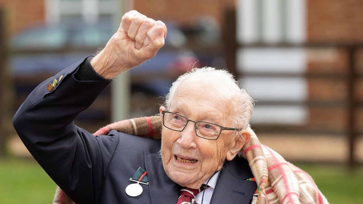 In this file handout photo released on April 30, 2020, shows Captain Tom Moore shows Captain Tom Moore waving at a flypast by Battle of Britain Memorial planes to celebrate his 100th birthday in Marston Moretaine