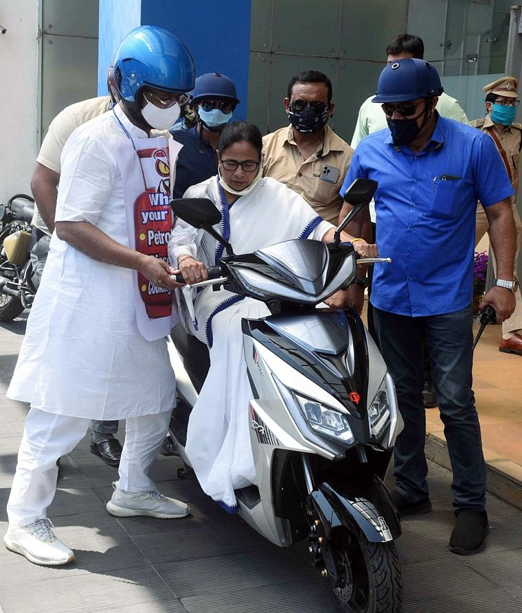 Chief Minister Mamata Banerjee along with Mayor of Kolkata Firhad Hakim rides an electric scooter as a mark of protest against rising fuel prices, in Kolkata