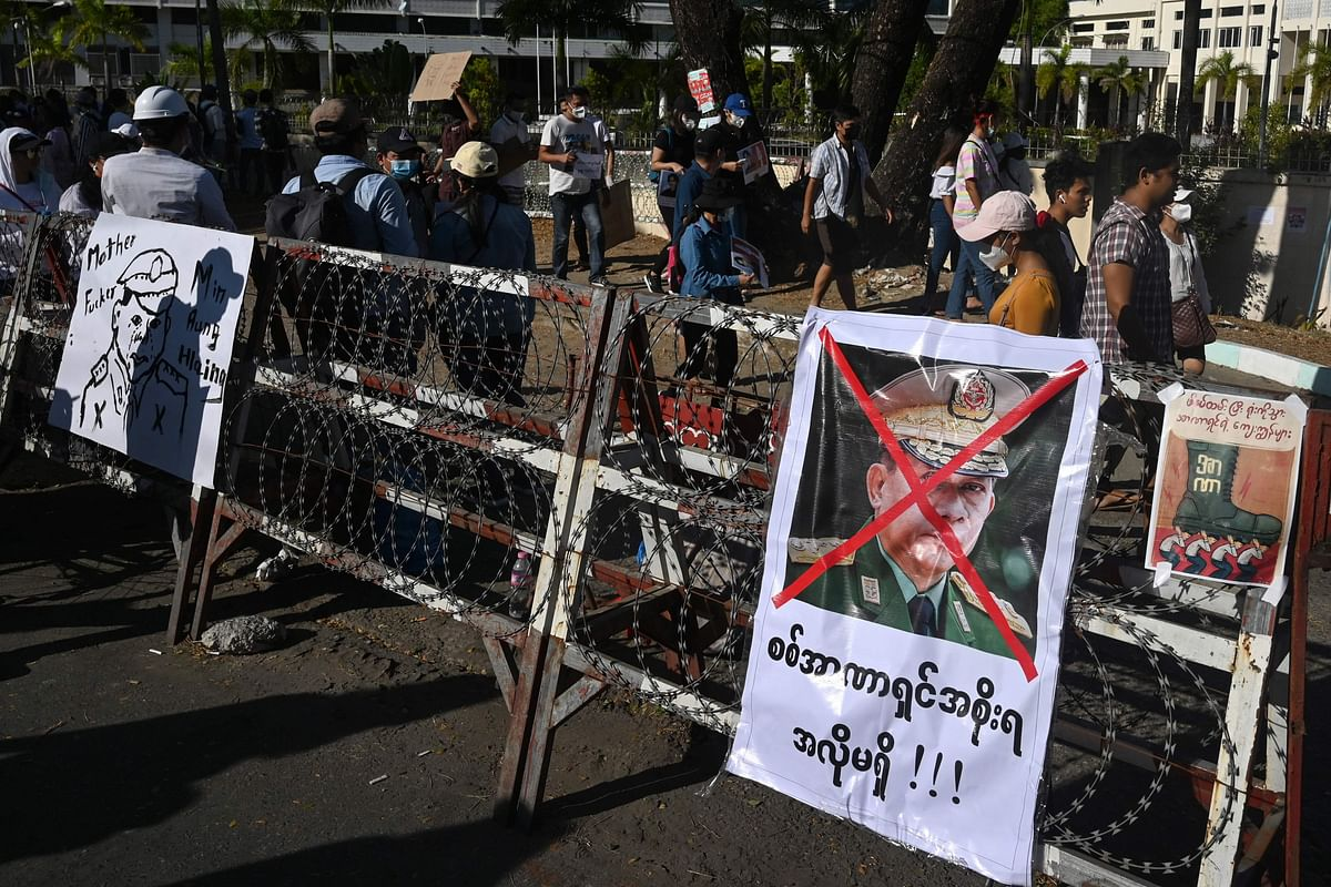 A poster featuring army chief Senior General Min Aung Hlaing is displayed on a barricade as protesters take part in a demonstration against the military coup in front of the Central Bank of Myanmar in Yangon on February 11, 2021.