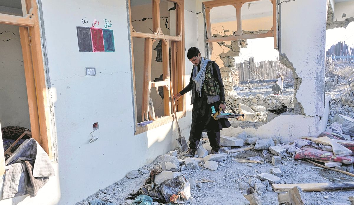Afghan security officer inspect the site of a car bomb attack that targeted a security outpost in Khogyani district of Nangarhar province on February 7, 2021.