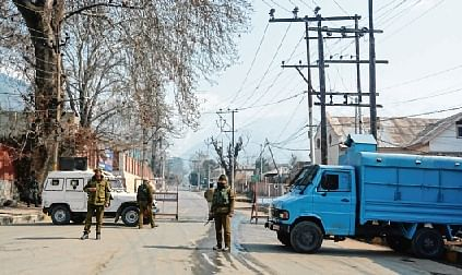 Security men stand guard outside house of former J&K CMs Omar Abdullah and Dr Farooq Abdullah, in Srinagar on Sunday.