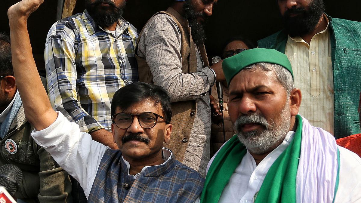 Shiv Sena leader Sanjay Raut along with BKU leader Rakesh Tikait during farmers ongoing protest against farm laws at Delhi-Gazipur border, in Delhi on Tuesday.