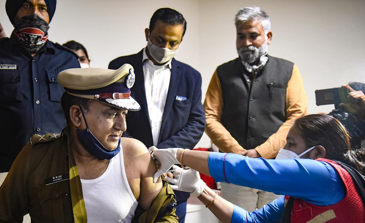 A medic administers Covishield vaccine dose Police Commissioner K K Rao in the presence of Haryana Home Minister Anil Vij (R) after the virtual launch of COVID-19 vaccination, in Gurugram, on Feb. 4, 2021.