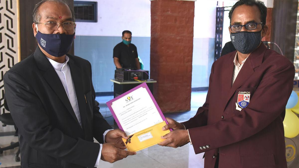 Principal Campion school Fr. Athnas Lakra SJ giving award to teacher Mahendra Kothari
