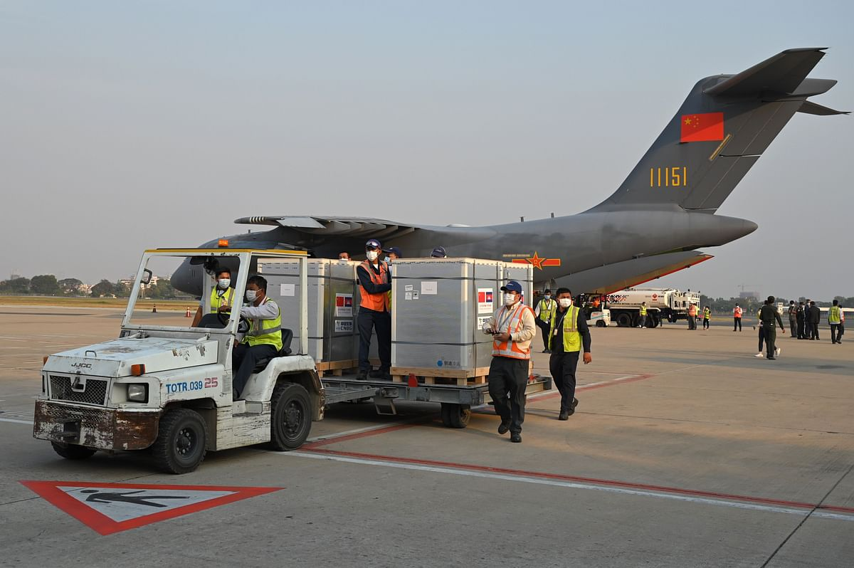Workers transport a shipment of Sinopharm Covid-19 coronavirus vaccine from a Chinese military plane at Phnom Penh International Airport in Phnom Penh, Cambodia, on February 7, 2021.