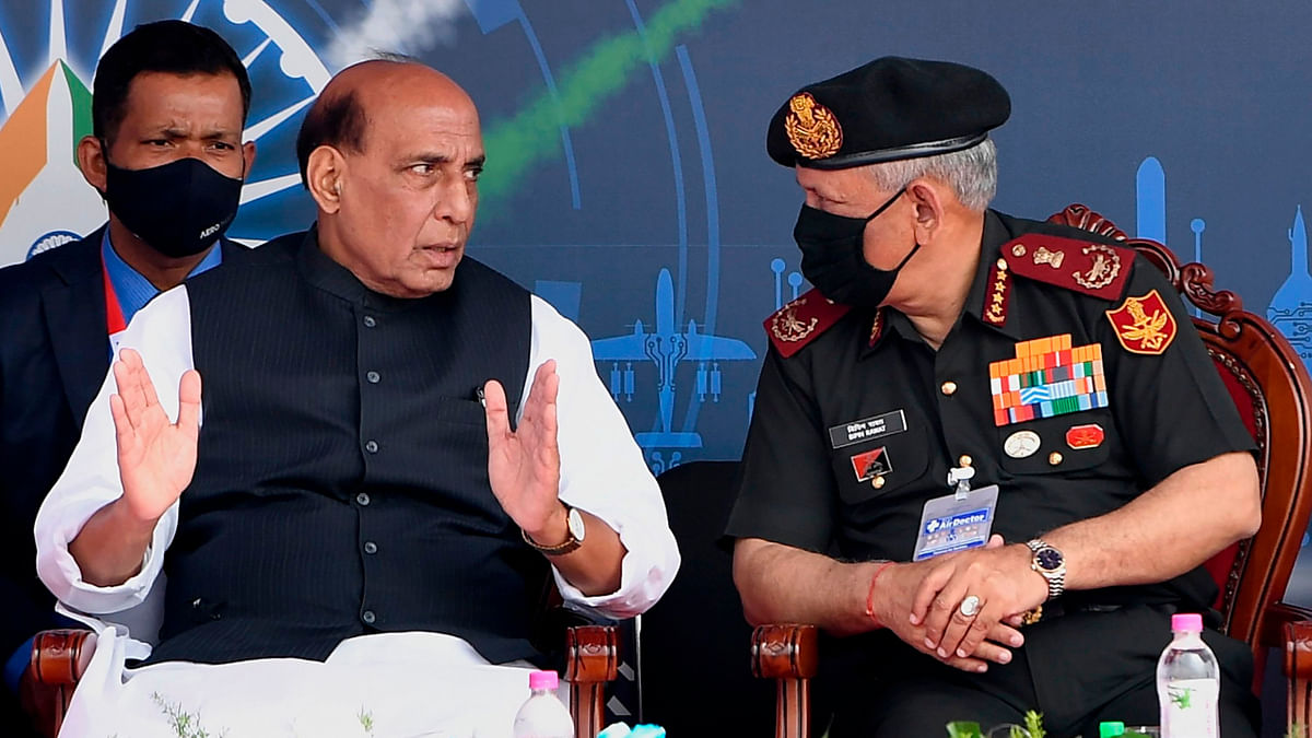 Union Defence Minister Rajnath Singh speaks with Chief of Defence Staff General Bipin Rawat (R) during the inaugural ceremony of the Aero India 2021 Airshow at the Yelahanka Air Force Station in Bangalore on February 3, 2021.