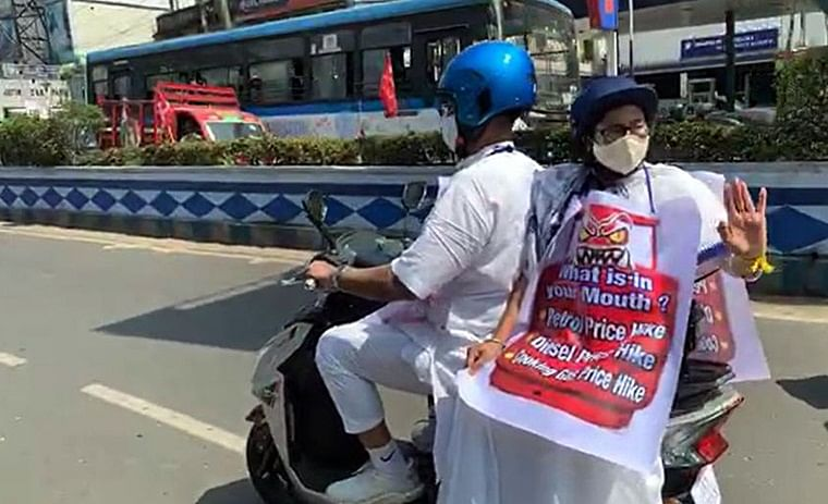 With a placard protesting against the petrol price hike hanging around her neck, helmet-clad Banerjee waved at people on both sides of the road